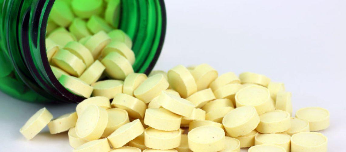 Folic acid spilling from green pill bottle